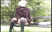 Young blonde peeing on a wooden bench