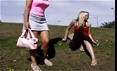 Two blonde girls peeing on a hill