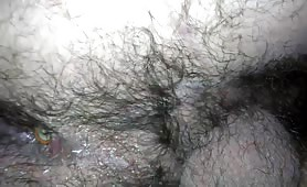 Hairy man pooping a battery in close up