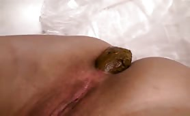 Sexy wife shitting a long brown turd in close up