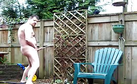 Mature gay guy peeing on his flowers in the garden