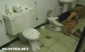 Two blonde girls peeing and pooping into a fake toilet