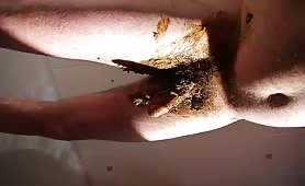 Rubbing brown poop on his long cock