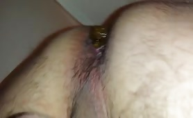 Holding his cock while shitting a big turd