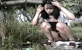 Petite Japanese shitting outdoor on the ground