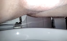 Shaved balls in very close up while shitting