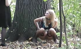 Blonde girl peeing in the middle of the woods