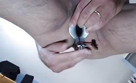 Crazy guy examines ass with speculum