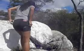 Sexy babe peeing in the rocks