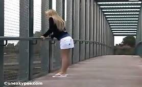 Blonde peeing on the bridge