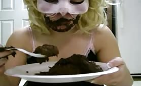 masked woman eating scat from a plate